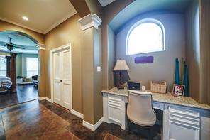 Desk area in master can double as a sit-down vanity. Note the arches, crown molding, granite and great natural light.