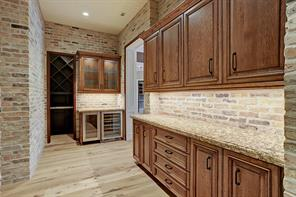 BUTLER'S PANTRY with wine and beverage chillers, glass-fronted cabinets with glass shelving and lights, solid-fronted cabinets and deep drawers, and the opening into a spacious WINE CLOSET.