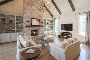The living room's beauty is punctuated by a 22' soaring brick surround fireplace that serves as the centerpiece of the room.  It is a marvelous, comfortable space with wood beams, vaulted ceiling and built-in bookcases that adds practicality to the room.