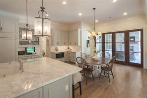 The generously sized kitchen and breakfast area is highlighted as extra wide divided light doors artfully mesh the indoors with the outdoor living area.  Note the multi-piece molding and recessed lighting.  Dual custom lanterns adorn the kitchen island.