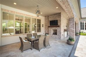 The covered patio serves as a wonderful extension of tranquil living.   The brick fireplace with flat screen Smart TV serves as the centerpiece of the comfortable area.  Note hardwood beadboard ceiling, wood beam fireplace mantel and hanging gas lantern.