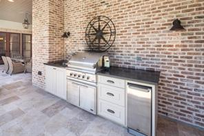 Perfect for outdoor entertaining, the handsome brick wall serves as the backdrop for the outdoor kitchen area featuring Farmhouse sconces, Indian premium home black countertops, stainless sink/beverage cooler, DCS Fisher & Paykel gas grill, and 15'' Whytner stainless steel undercounter fridge.