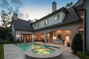 Alluring outdoor spaces are showcased as one views the gorgeous pool and hot tub accompanied by the inviting sheltered patio and summer kitchen. A pool bath and outdoor pool shower sit adjacent to the summer kitchen.