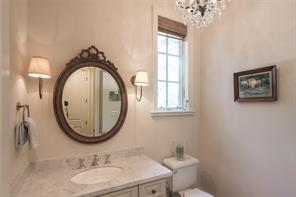 Beautiful designer touches abound in the powder room with dual sconces, Rococo iron and crystal chandelier, marble countertops, 11' ceiling and white oak flooring.