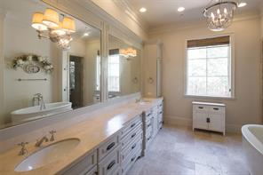 The quality-laden master bath features vintage Travertine French vintage quarter flooring with Versailles pattern, Torreon Travertine countertops, wainscoting framed mirrors, seamless spa shower with rain head shower and furniture quality cabinets with linen cabinets and soft close drawers.