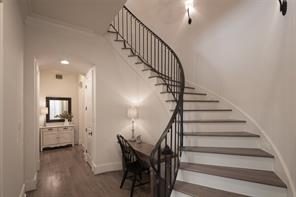 Winding staircase boasts white oak treads, French iron balustrade and step lighting.