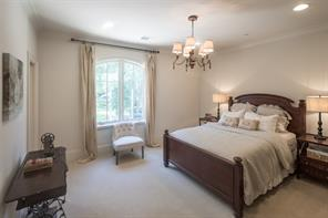 Well-appointed secondary bedroom enjoys pretty northern exposure, extended height baseboards, crown molding, recessed lighting, custom fitted walk-in closet.