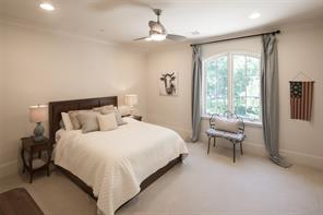 Secondary bedroom features crown molding, 3 blade ceiling fan, 9' ceiling and double divided light window extending a norther view.  Walk-in closet with custom hanging rods and built-in cabinetry.