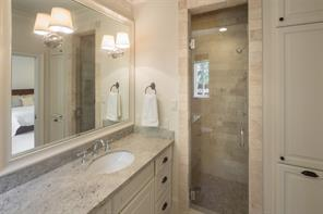 Nicely appointed secondary bath with mounted sconces, limestone Salem gray flooring, Kashmir cream granite countertop and subway tile surround shower with seating.