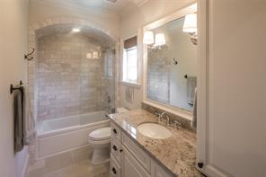 Exceptional bath with subway tile surround in jetted tub/shower, seamless glass door, granite countertop and two mounted sconces.