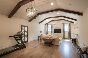 The game room extends hints of farmhouse architecture with its wood beamed vaulted ceilings, hardwood floors and access to the Juliet balcony overlooking the living room. Adjacent game room powder bath with Kashmir granite countertops and white oak flooring.