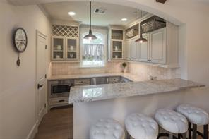 A charming nook is home to the game room bar that is replete with granite countertops, wine rack, undercounter beverage refrigerator, ice maker and built in microwave.