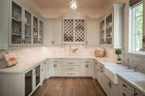 Remarkable butler's pantry boasts glass front cabinetry, Bianco Carrara polished marble countertops and Carrara subway tile backsplash. An undermount refrigerator, Wolf warming drawer, wine rack, and ice maker add to its convenience.