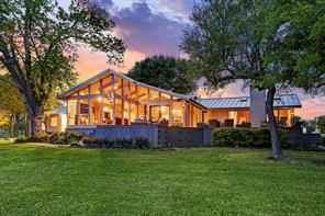 The contemporary single story stone faced residence is located just off the Cedar hill Road gated entrance and positioned on a hilltop overlooking the rolling landscape dotted with majestic trees and a large five acre lake.