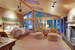 The Master Bedroom (20 X 18) is a restful retreat with its hardwood flooring, wood planked walls, brick-lined fireplace with granite surround/wood mantel, windowed wall with shades, double door to wrap-around porch pitched ceiling with fan, three skylights with motorized shades and spot lighting.