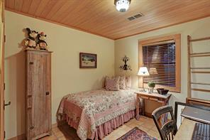 One of three Guest Bedrooms - this one (12 X 10) features Saltillo tile flooring, wood planked ceiling, painted walls rustic light fixture, crown/base molding and wood blinds.