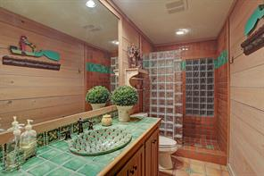 Across the hall from the first Guest Bedroom is the Guest Bath/Powder Room with its green tile countertop and decorative backsplash, bowl sink with bronze fixtures, wood planked walls, recessed lighting and walk-in shower with tile surround and glass-block divider.