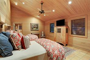 The second Guest Bedroom (20 X 15) features Saltillo tile flooring, pitched ceiling with fan, wood planked walls/ceiling, recessed lighting, windows with blinds and en suite bath.