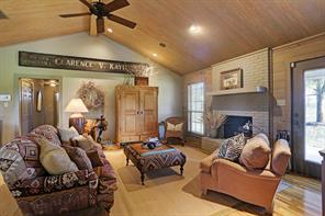 The Living/Dining Room (18 X 18) includes hardwood flooring, gas/wood burning fireplace with brick surround, door to patio, wood planked ceiling, pitched ceiling with fan, built-in speakers and recessed lighting.