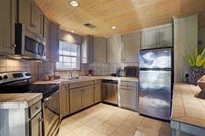 The Kitchen (12 X 8) is fully equipped for the occasional guest with its tile flooring, tile countertop and backsplash, breakfast bar, door to patio and GE stainless appliances.