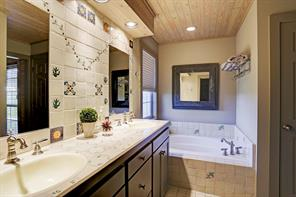 The Guest Bath is cleverly finished with tile flooring, tile countertops and decorative backsplash, wood planked ceiling with recessed lighting, two sinks with cabinet storage below, Kohler soaking tub, glass front walk-in shower with decorative tile surround, separate water closet and walk-in closet with shelving and drawers.