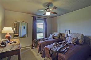 The third Guest Bedroom (12 X 11) includes carpeted flooring, painted walls, ceiling fan and window with drapery.
