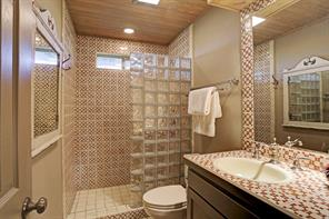 The second and third Guest Bedrooms share an adjacent Bath as shown here with tile flooring, decorative tile countertops and backsplash, wood planked ceiling, walk-in shower with tile surround and glass-block divider.