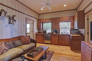 The front Living/Kitchenette of the Stables' apartment is charming with its hardwood flooring, wood planked walls with decorative wood accent borders and wood kitchen cabinets with tile countertops.