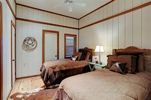 The first Guest Bedroom (11 X 10) is cozy with its hardwood flooring wood planked walls with decorative wood border ceiling fan, closet and en suite bath.