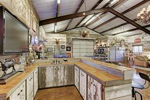 Unique to the Cedar Hill Farm is the Party Barn (58 X 38) which is a great space to entertain groups of guests.  Notice the high pitched ceiling with exposed rafters.  Reclaimed barn wood decorates the interior walls and create a warm and comfortable ambiance.  The stained concrete flooring is easy to maintain.  A decorative chandelier adds an easy elegance to the space the two roll up doors open easily to the outdoors.