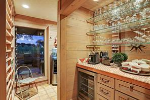 The Wet Bar is conveniently located close to the Kitchen and features a mirrored wall with glass shelving, stainless GE mini refrigerator.
