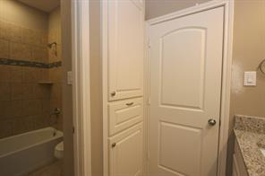 Linen/storage cabinets within full bath.