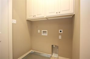 Utility closet has upper cabinets.