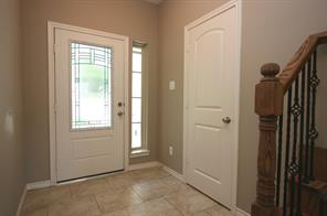 Leaded glass front door with tile flooring throughout bottom floor. Door to the right is the powder bath.
