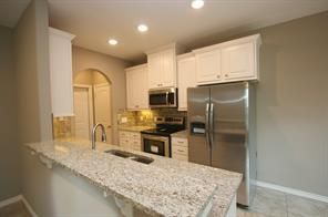 Kitchen has granite counters, stainless appliances and comes with a brand new refrigerator!