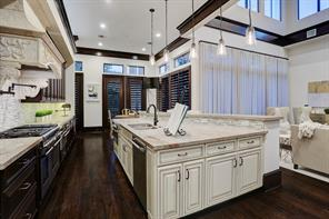 A closer look at the GOURMET KITCHEN with a stunning vent hood with carved front and sides above the professional gas range, and a huge amount of granite-topped prep space on the island.