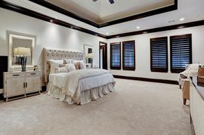 The MASTER SUITE is spacious with a high tray ceiling with fan, plush neutral carpeting, shuttered windows and ample room for large-scale furniture.