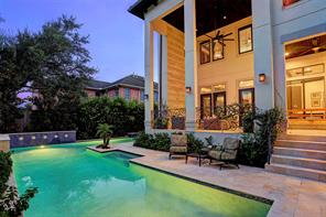 The L-Shaped HEATED POOL, with a spa and fountains, is so inviting.  Notice the wide tile coping around the pool and the 2-story covered back porch with fireplace and ceiling fans.