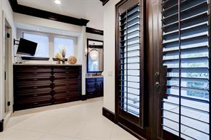 The MASTER DRESSING ROOM has a built-in dresser, a sumptuous master bathroom, private water closet, a large customized closet, and an Outdoor Covered Patio to the Right.