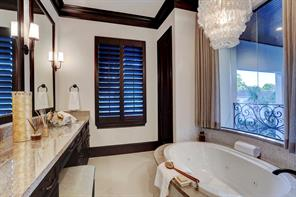 There is a DOUBLE VANITY with granite top and a deep, jetted soaking tub with an elegant chandelier above.