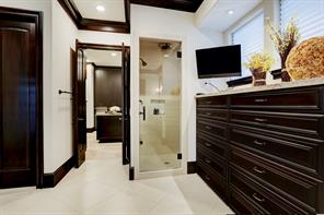 The MASTER BATH & DRESSING ROOM has a steam shower with a seamless glass door, and beyond that is a customized closet.