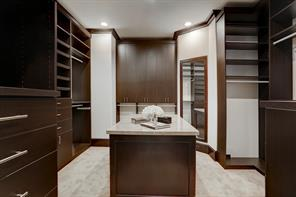 MASTER CLOSET with an island and a ton of hanging space and shoe shelving.  Also included are drawers and cabinets.