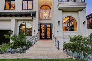 Majestic metal door with glass inserts covered by scrolled wrought iron welcome you and your guests to this visually stunning home!