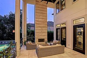 A close up view of the COVERED BACK PORCH.  Notice the exquisite fireplace with the travertine surround and wall.  Plenty of room for an outdoor living room or dining space.