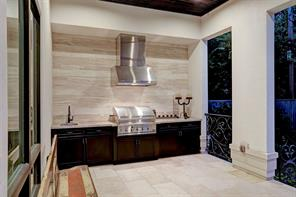 SUMMER KITCHEN with gas grill and powerful vent hood above, a sink and excellent granite prep space.