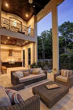 A larger view of the COVERED BACK PORCH, Summer Kitchen beyond and the Balcony off the Master Suite above.