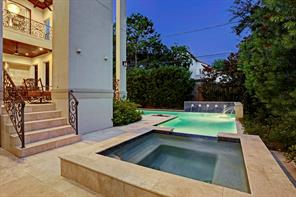The HEATED SPA is at the end of the heated pool, and up the stairs on the left to the COVERED BACK PORCH.