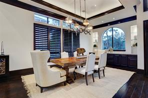 The FORMAL DINING ROOM has a tray ceiling with cove lighting, a fashionable chandelier and a built-in buffet and cabinets at the end of the room.  Notice the lit glass shelving above the buffet.  So pretty!