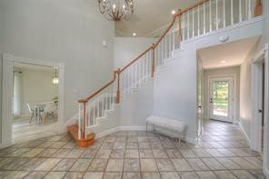 Two-story entry foyer features staircase with architectural details and large chandelier.