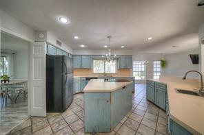 Large kitchen with custom painted distressed blue cabinets. Large island and lots of counter space in this kitchen! Window at the double sink looks out onto the front porch.